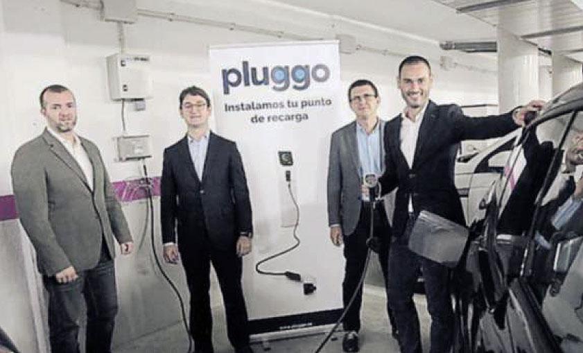 Los fundadores de Pluggo con un punto de recarga de coche eléctrico
